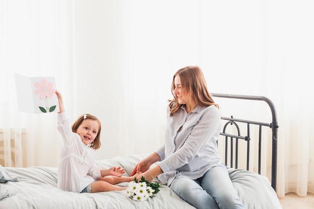 Gelukkige moeder en dochter met groetkaart op bed