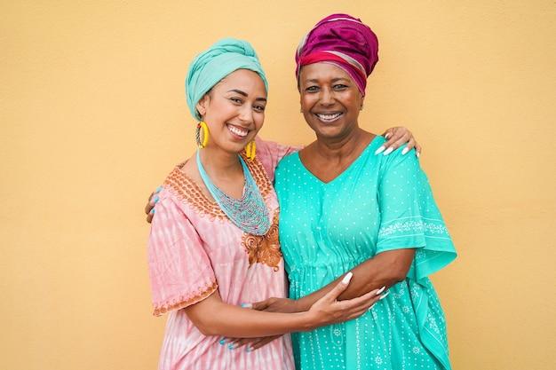 Gelukkige moeder en dochter met traditionele afrikaanse jurken poseren en glimlachen