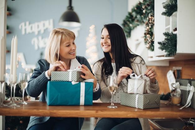 Gelukkige moeder en dochter pakken kerstcadeaus uit