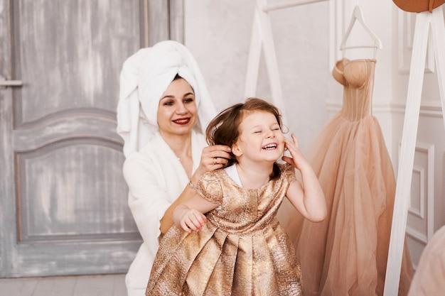 Gelukkige moeder en dochter trekken een jurk aan