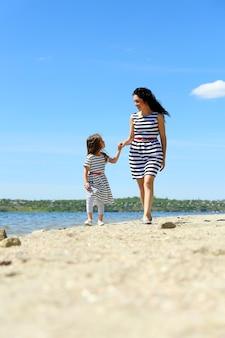 Gelukkige moeder en dochter. wandeling op het strand