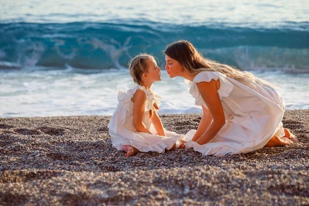 Gelukkige moeder en dochter zitten samen en kussen elkaar in kust in witte jurk tijdens zonsondergang.