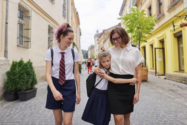 Gelukkige moeder en dochters die naar school gaan.