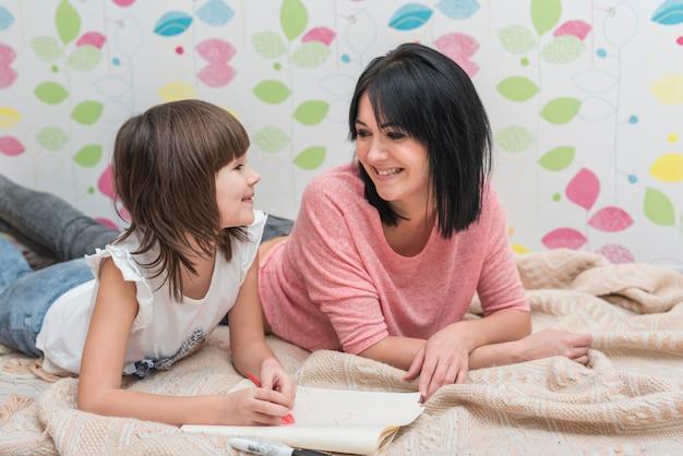 Gelukkige moeder en dochtertekening die op bed liggen