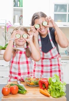 Gelukkige moeder en dochtertje spelen met plakjes courgette op de ogen thuis keuken