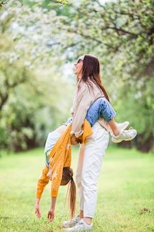 Gelukkige moeder en haar dochter die buiten in het park plezier hebben