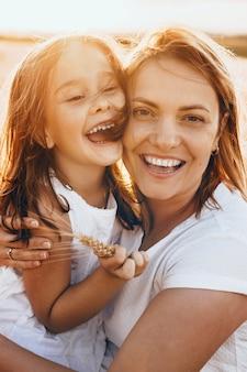 Gelukkige moeder en haar dochter die in de zon met tarwezaden stellen die bij camera glimlachen