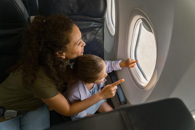 Gelukkige moeder en haar dochter kijken naar het landschap buiten het vliegtuigraam