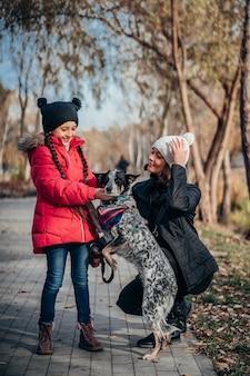 Gelukkige moeder en haar dochter lopen met hond in herfst park