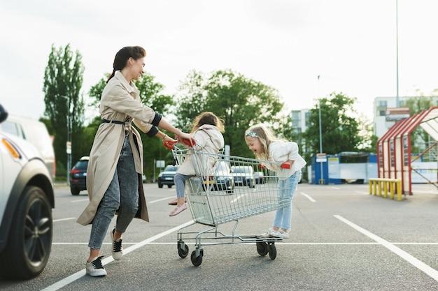 Gelukkige moeder en haar dochters hebben plezier met een winkelwagentje