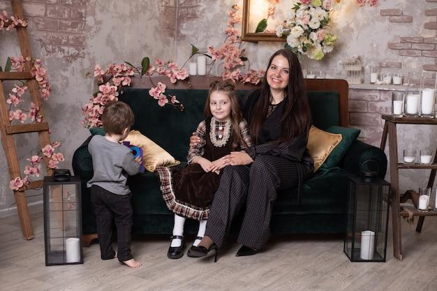 Gelukkige moeder en haar dochtertje en zoon, gelukkig lachend familie op sofa thuis