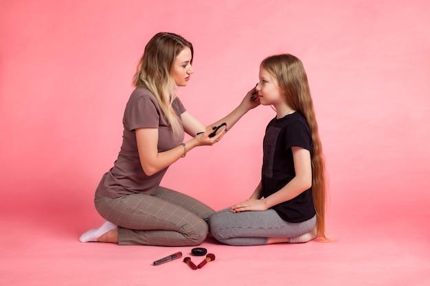 Gelukkige moeder en haar dochtertje in vrijetijdskleding zitten, houden borstels vast en doen make-up voor elkaar op roze achtergrond. concept van tijd doorbrengen samen met kinderen en familierelaties