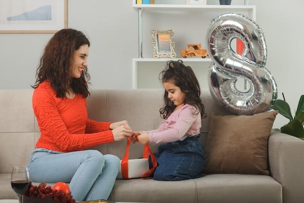Gelukkige moeder en haar dochtertje zitten op een bank die samen een cadeau inpakt en vrolijk lacht in een lichte woonkamer die internationale vrouwendag 8 maart viert