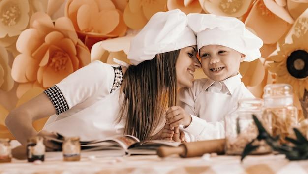 Gelukkige moeder en haar kind in de vorm van chef-koks bereiden een feest voor