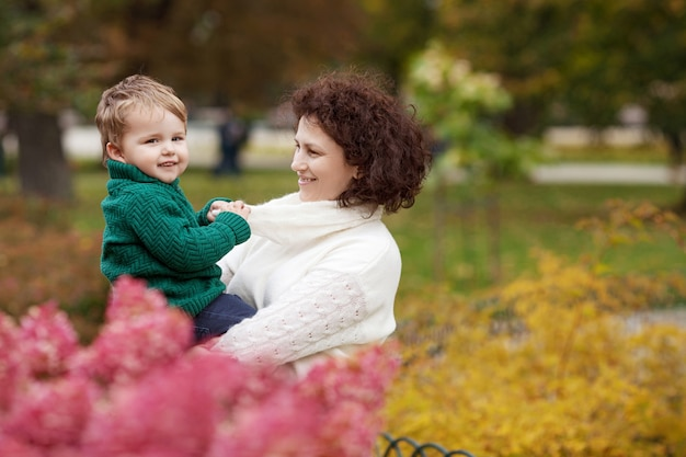 Gelukkige moeder en haar kleine jongen kind spelen met moeder in het park moeder en zoon omarmen