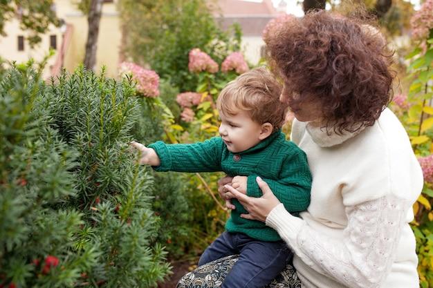Gelukkige moeder en haar kleine jongen kind spelen met moeder in het park moeder en zoon omhelzen kind