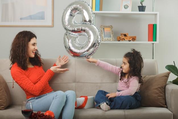 Gelukkige moeder en haar kleine kind dochter zittend op een bank met nummer acht gevormde ballon glimlachend vrolijk samen plezier hebben in lichte woonkamer vieren internationale vrouwendag 8 maart