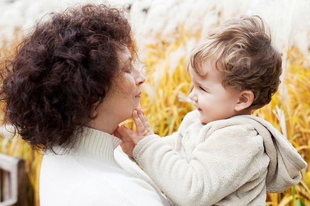 Gelukkige moeder en haar kleine kind. glimlachend kind spelen met moeder in het park. moeder en zoon omarmen.