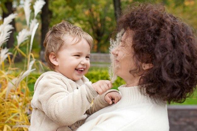 Gelukkige moeder en haar kleine kind. het glimlachen kind het spelen met moeder in het park.