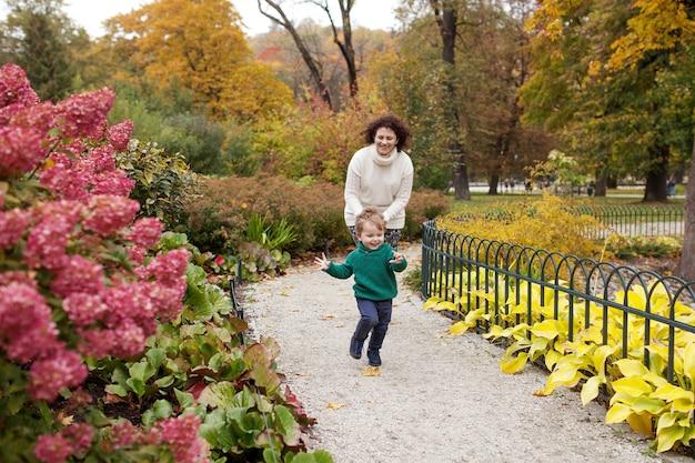 Gelukkige moeder en haar kleine kind wandelen in het park gelach moeder en zoon spelen en rennen naar binnen