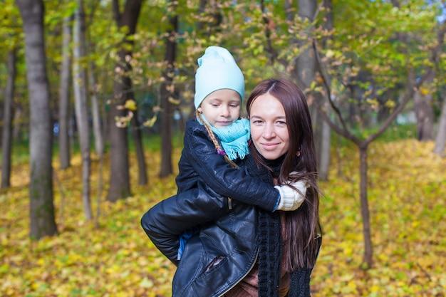 Gelukkige moeder en haar leuke dochter die pret in geel de herfstbos hebben op een warme zonnige dag