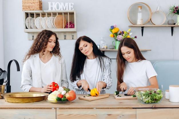 Gelukkige moeder en haar leuke dochters die groenten in de keuken snijden.