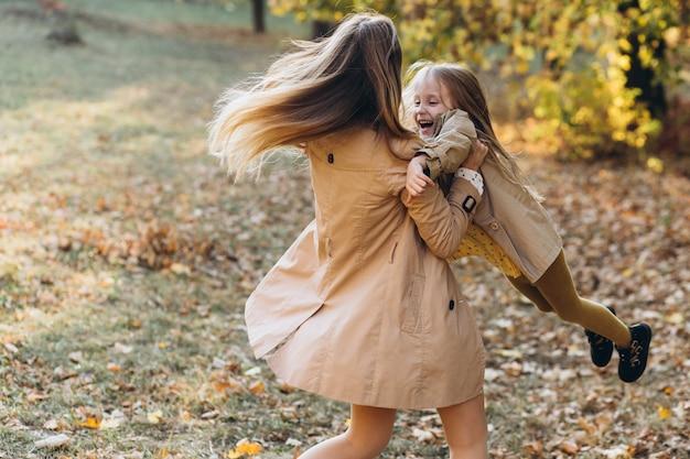 Gelukkige moeder en haar mooie dochter hebben plezier en wandelen in het herfstpark.