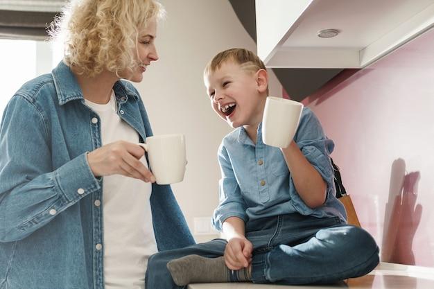 Gelukkige moeder en haar schattige zoon die thee drinken in de keuken