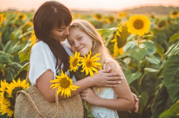 Gelukkige moeder en haar tienerdochter op het zonnebloemgebied. levensstijl geluk buitenshuis