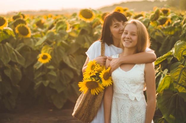 Gelukkige moeder en haar tienerdochter op het zonnebloemgebied