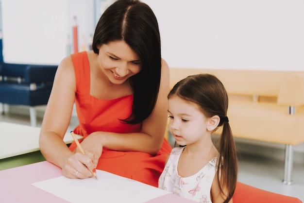 Gelukkige moeder en kind hebben plezier bij kinderkliniek.