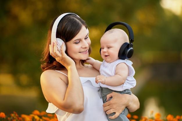 Gelukkige moeder en kind in draadloze koptelefoon tijdens het buiten wandelen
