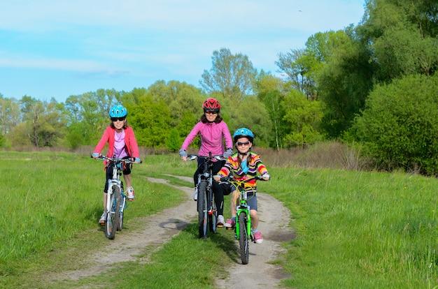 Gelukkige moeder en kinderen op fietsen buiten fietsen, actieve familiesport