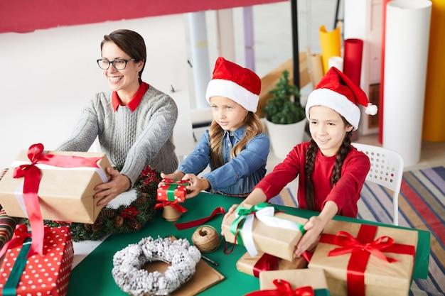 Gelukkige moeder en kinderen wisselen kerstcadeautjes uit