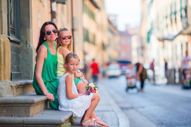 Gelukkige moeder en kleine schattige meisjes op gezellige straat tijdens italiaanse vakantie. familie europese vakantie.