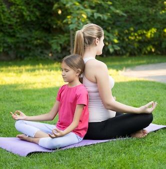 Gelukkige moeder en lachende dochter die yoga beoefent en rug aan rug zit