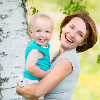 Gelukkige moeder en peuterzoon bij veld - openluchtportret