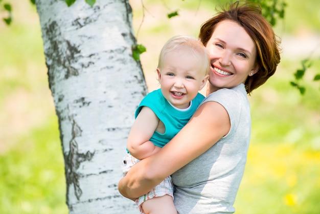 Gelukkige moeder en peuterzoon bij veld