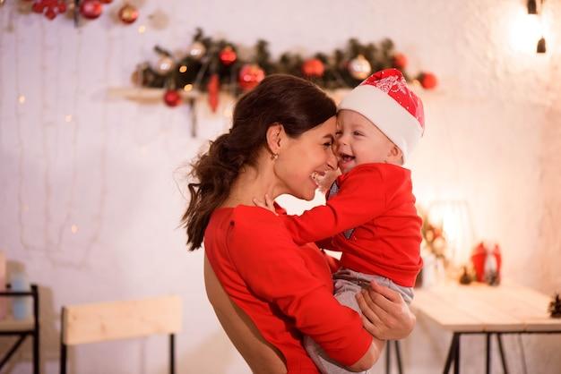 Gelukkige moeder en schattige baby in kerstmuts vieren kerstmis