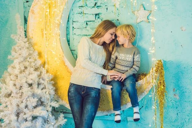 Gelukkige moeder en schattige jongen vieren kerstmis. nieuwjaars vakantie Premium Foto