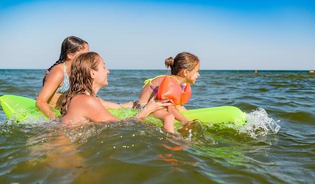 Gelukkige moeder en twee kleine positieve dochters baden en zwemmen in de zee met een luchtbed op een zonnige zomerdag