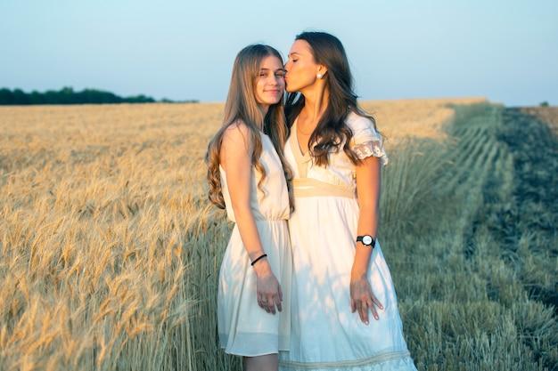 Gelukkige moeder en volwassen dochter staan samen in de buurt van het tarweveld in het licht van de avondzon
