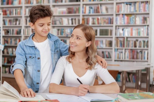 Gelukkige moeder en zoon die bij elkaar glimlachen terwijl het doen van huiswerk bij de bibliotheek
