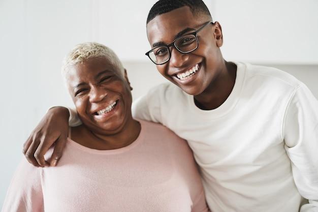 Gelukkige moeder en zoon die elkaar thuis koesteren - focus op jongensgezicht