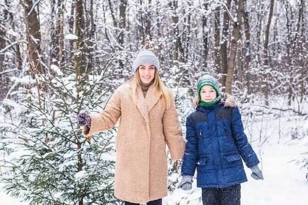 Gelukkige moeder en zoon die pret hebben en met sneeuw in de winter spelen