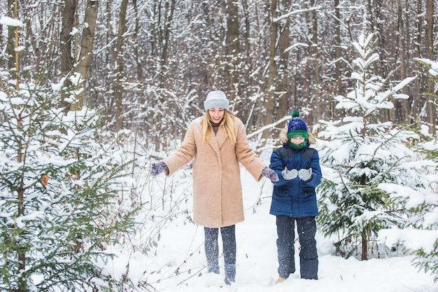 Gelukkige moeder en zoon die pret hebben en met sneeuw in de winterbos spelen.