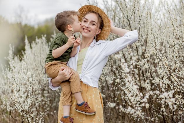 Gelukkige moeder en zoon die samen plezier hebben. moeder knuffelt haar zoon zachtjes.