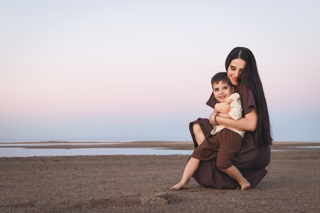 Gelukkige moeder en zoon hebben samen plezier moeder knuffelt zachtjes haar kleine schattige zoon buiten