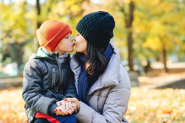 Gelukkige moeder en zoon in de herfst. moeder en kind kussen buitenshuis.