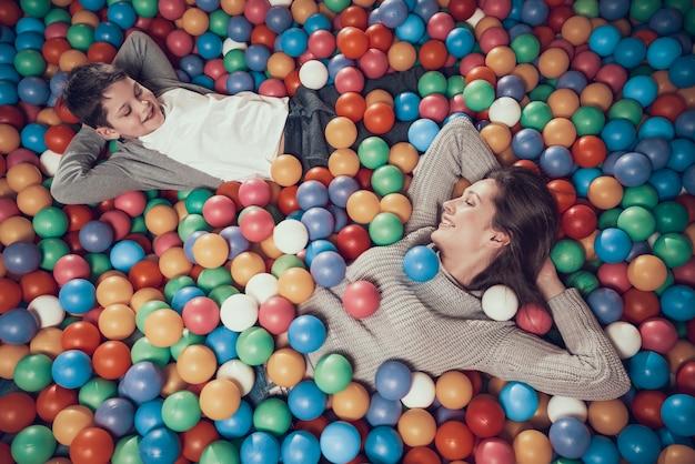 Gelukkige moeder en zoon in pool met ballen